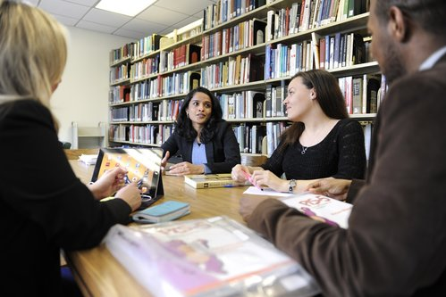 Group of people talking at a table with books in the background.