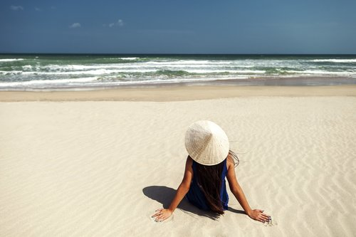 girl in tropics with vietnamese hat on the beach