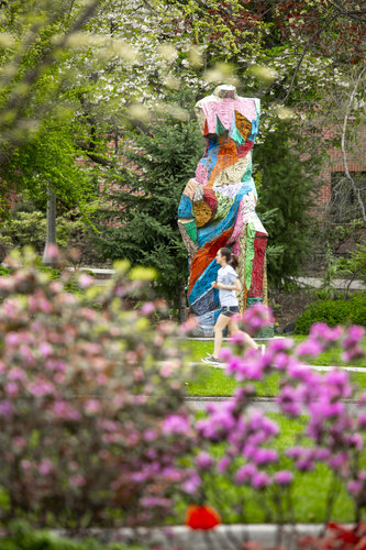 A student jogs by the sculpture near Douglas Hall.