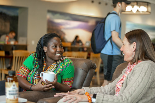 Susan Prudente of the Student Engagement Center chats with senior Laurinda Nyarko of Ghana in the Jewett Cafe in April 2019.