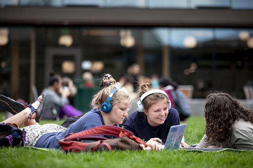 Students hang out on the grass and study or eat lunch between Cleveland Commons and Stanton Hall