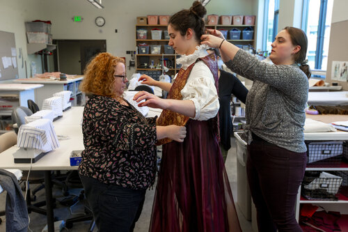 "Costume Director and Visiting Professor Annaliese Baker (red hair), assistant costume director Eliza Van De Rostyne (black shirt), and Grace Sanwald '21, fit a costume to Ruby Daniel '20 for the spring 2019 performance of ""Life is a Dream"" in Harper Joy Theatre's costume shop."
