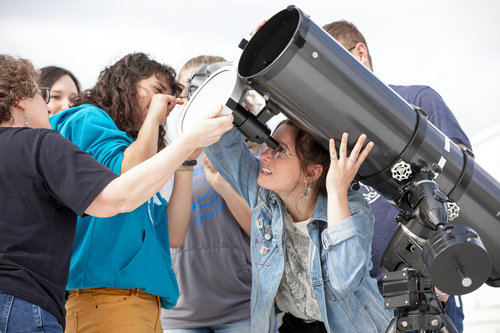 Students in Andrea Dobson's ASTR 178 class use a sun funnel on a telescope to study the sun on a spring day on the roof of the Hall of Science. Students are: Skylar Grayson '21 (red shirt, brown hair); Rainier Naylor '22 (blue sweatshirt); Carmen Tappero '21 (gray sweatshirt); Katy Laliotis '21 (jean jacket); and Michael Daniel '20 (Whitman shirt, glasses).