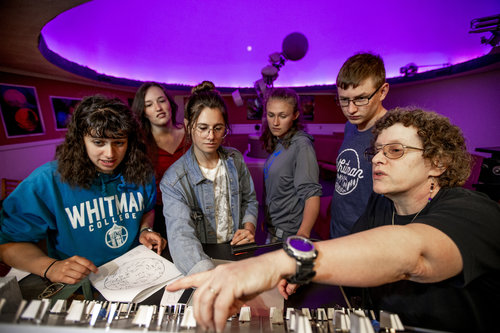 Associate Professor Andrea Dobson shows students how to work the controls in the planetarium inside the Hall of Science. Students are: Skylar Grayson '21 (red shirt, brown hair); Rainier Naylor '22 (blue sweatshirt); Carmen Tappero '21 (gray sweatshirt); Katy Laliotis '21 (jean jacket); and Michael Daniel '20 (Whitman shirt, glasses).