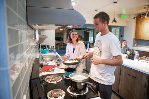 Cole Sibelius '22 cooks burritos with Maddie Ott '22 in the Lyman Kitchen in April 2019.