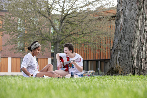 Students play guitar and sit on the grass outside Stanton Hall in spring 2019.