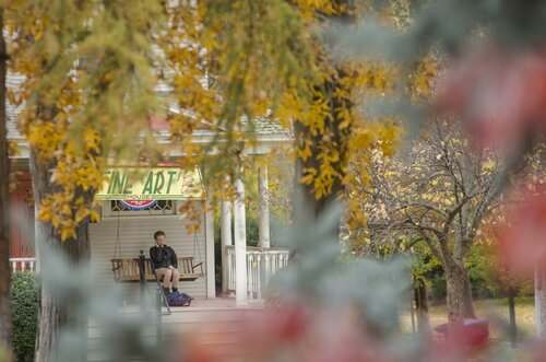 A student studies on the porch of the Fine Arts House in 2014.